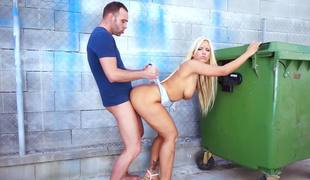 A blonde is getting banged doggystyle outside in the street