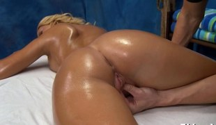 Dreamy blonde with tanned body rubbed on a massage table