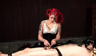 Dominatrix-bitch with flaming hair restrains her tied slave's wang and balls with chains