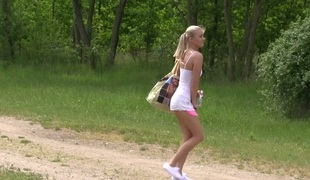 Golden-haired sweetie Cayla A rubs her shaved coochie on green grass